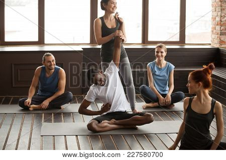 Fitness Instructor Helping African Man Beginner With Stiff Back Developing Flexibility Holding His A
