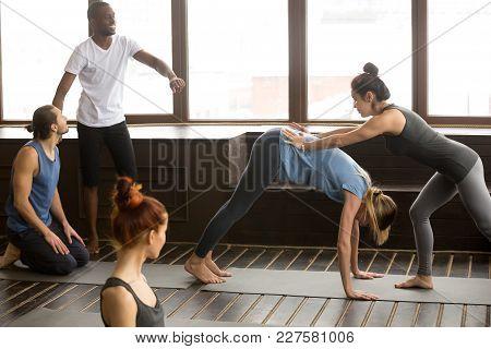 Yoga Teacher Assisting Woman Doing Downward Facing Dog Exercise Standing In Adho Mukha Svanasana Pos