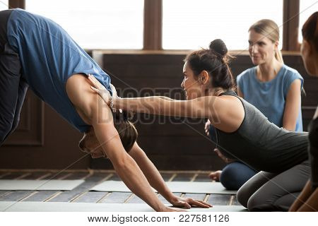 Smiling Yoga Teacher Or Pilates Instructor Helping Young Man To Stretch Muscles Holding Hands On His