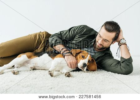 Handsome Man Lying On Carpet With Dog Isolated On White