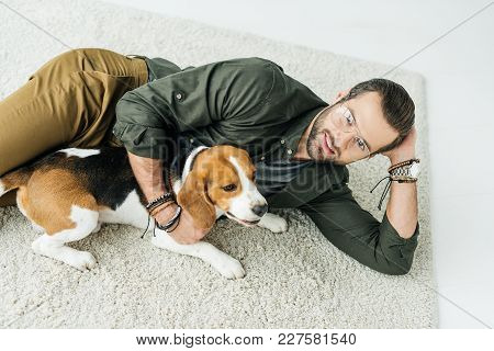 High Angle View Of Handsome Man Lying On Carpet With Cute Beagle And Looking At Camera