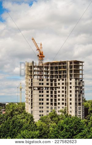 Construction Of House. High-rise Tower Crane With A Multi-storey Building Under Construction.