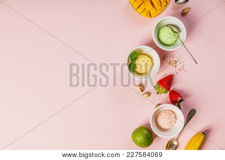 Top view of ice cream in white bowls and fresh ingredients  on pink shabby chic vintage background. Pink (strawberry), yellow (mango or banana) and green (lime, green tea or pistachio).