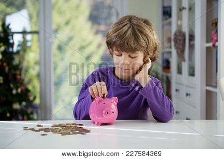Little boy putting coins into piggy bank. Learning financial responsibility and projecting savings.