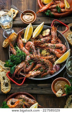 Seafood Dinner. Grilled Tiger Prawns In Grilling Pan With Fresh Lemon, Garlic, Bread Over Wooden Bac