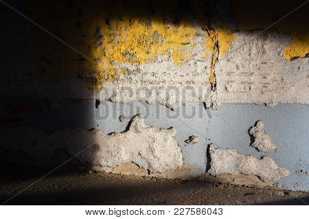 Light Disclosed A Rundown Wall In Yellow And Gray