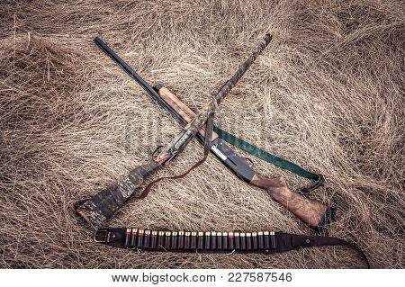 Hunting Shotguns On Dry Grass On Haystack As Hunting Background In Wild West Style
