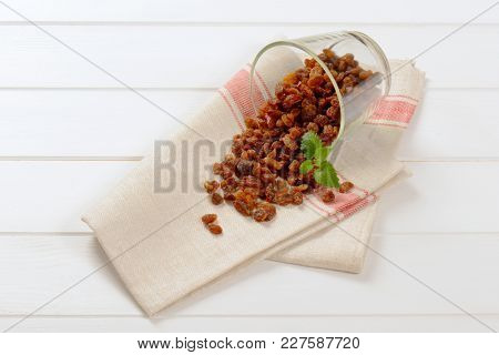 glass of sweet raisins spilt out on place mat