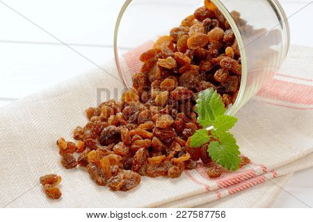 glass of sweet raisins spilt out on place mat - close up