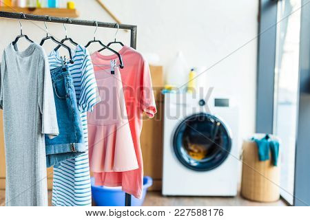 Clothes On Hangers And Washing Machine At Home