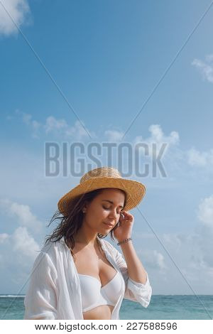 Young Woman In A White Bathing Suit And Hat Sunbathing On The Beach On A Background Of The Ocean