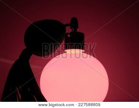 Glowing Vintage Pink Perfume Bottle In Red Background. Very Sexy And Passionable Atmosphere