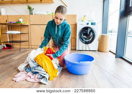 Young Woman Holding Clothes While Kneeling Near Plastic Basin And Washing Machine