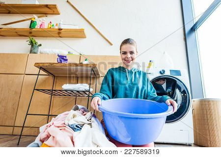 Young Woman Holding Plastic Basin And Smiling At Camera While Kneeling Near Clothes And Washing Mach