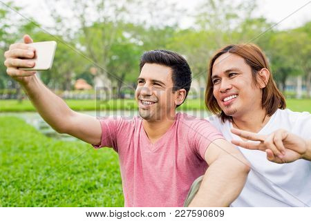 Closeup Portrait Of Two Smiling Handsome Young Men Posing, Showing Victory Sign And Taking Selfie Ph