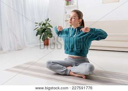 Girl Sitting In Lotus Position And Stretching On Yoga Mat At Home