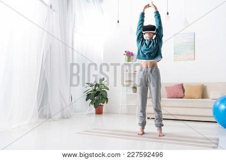 Girl Doing Yoga With Virtual Reality Headset On Yoga Mat At Home