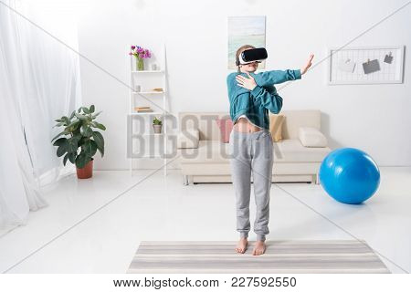 Girl Stretching Hands With Virtual Reality Headset On Yoga Mat At Home