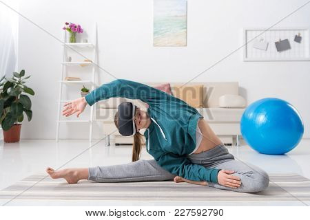 Girl Stretching Body With Virtual Reality Headset On Yoga Mat At Home