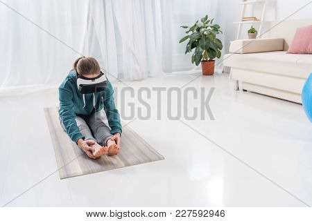 Girl Stretching Back With Virtual Reality Headset On Yoga Mat At Home