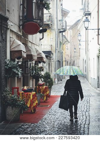 Woman With Blue Umbrella Walks On Quaint Cobblestone Alleyway In Aosta, Italy With Inviting Red Carp
