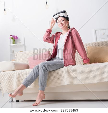 Smiling Girl Holding Virtual Reality Headset And Looking Away At Home