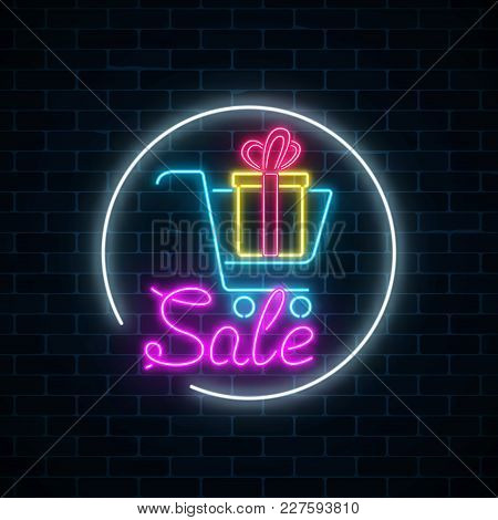 Glowing Neon Sign Of Supermarket Shopping Cart With Gift Box On A Dark Brick Wall Background. Lumino