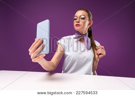 Girl Taking Selfie With Smartphone Isolated On Purple