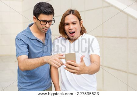 Closeup Portrait Of Two Surprised Handsome Young Men Using Smartphone Outdoors With Wall In Backgrou
