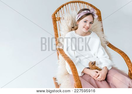Beautiful Girl Smiling At Camera While Holding Rabbit And Sitting In Rocking Chair Isolated On White