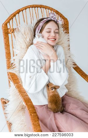Beautiful Happy Teenage Girl Hugging Rabbits While Sitting In Rocking Chair On White