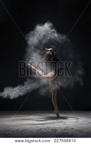 Woman In Undrewear And Pointe Shoes Jumping Gracefully In A White Dust Cloud Profile Shot In Dark Ro