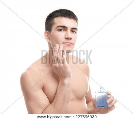 Handsome young man applying aftershave lotion on white background