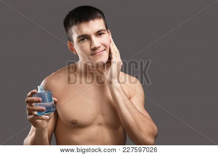 Handsome young man applying aftershave lotion against grey background