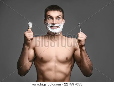 Emotional young man with shaving foam on his face holding brush and razor against grey background