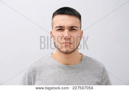 Emotional young man with dyed eyebrows on light background