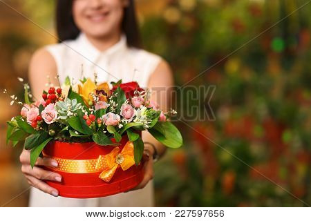 Woman with flowers in greenhouse. Small business owner