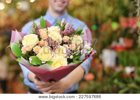 Man with flowers in greenhouse. Small business owner
