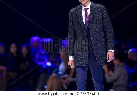 Male Model Walks The Runway In Stylish Suit During A Fashion Show. Fashion Catwalk Event Showing New
