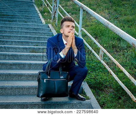 Sad Young Attractive Business Man Prayer Clasped Hands Dressed In A Blue Suit With A Red Tie Holding