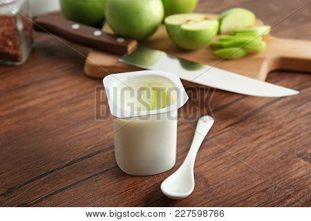 Plastic cup of yummy apple yogurt on wooden table