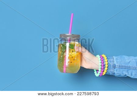 Young woman holding jar with lemonade on color background