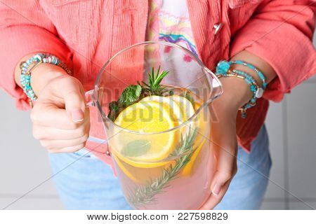 Young woman holding pitcher with pink lemonade, closeup