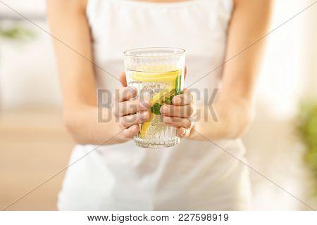 Young woman with glass of fresh lemonade, closeup