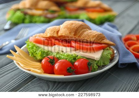 Plate with tasty croissant sandwich on table