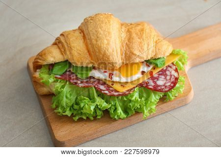 Wooden board with tasty croissant sandwich on table