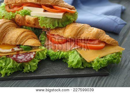 Tasty croissant sandwiches on table