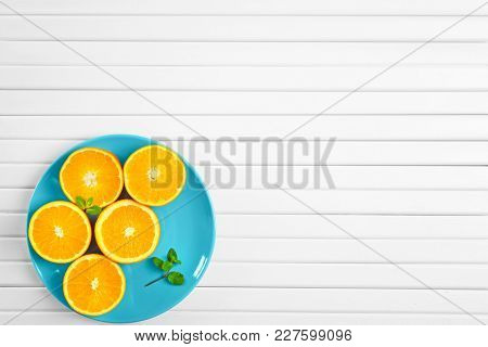 Plate with juicy ripe oranges on light background
