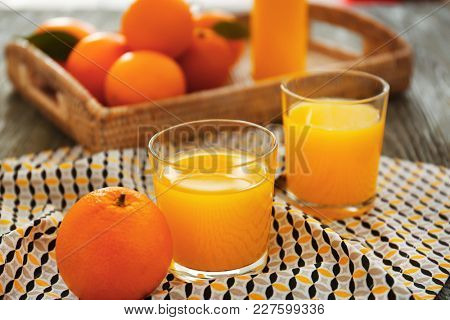 Glasses with fresh orange juice and fruit on table