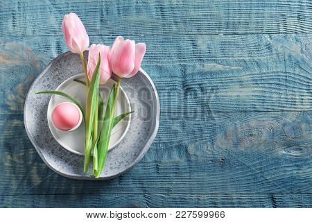 Beautiful festive Easter table setting with egg and tulips on wooden background
